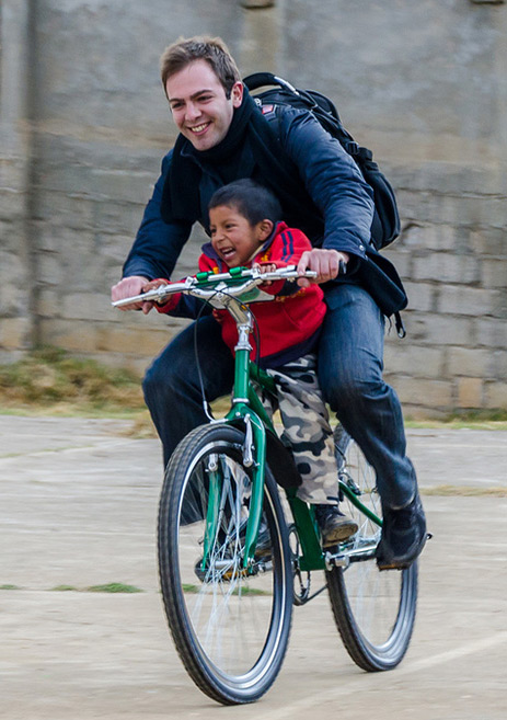 Pre-health post bacc medical alum Justin Haghverdian on bicycle with child
