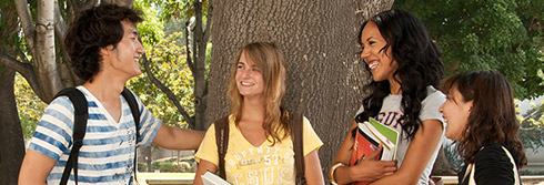 four students talking and smiling next to tree