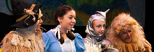 four young actors in wizard of oz costumes