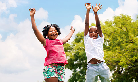 Two African American kids jumping high with joy